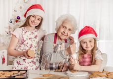 Grandmother With Granddaughters Soak Cream Decorating Cookies With Cream Royalty Free Stock Images