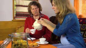 Grandmother woman and pregnant granddaughter drink marigold tea stock video