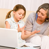 Grandmother and young girl with laptop learn count Royalty Free Stock Images