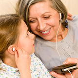 Grandmother and young girl listen music together Royalty Free Stock Images