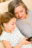 Grandmother and young girl listen music together. Granddaughter and grandmother listen to MP3 music headphones together smiling Royalty Free Stock Photo