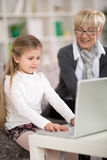 Grandmother with young girl use laptop together Royalty Free Stock Photography