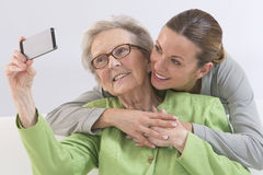 Grandmother and young grand-daughter photographing  themselves Stock Photos