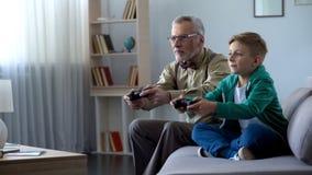 Grandpa и внук играя видеоигру с консолью, счастливое время совместно стоковая фотография rf