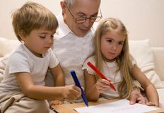 Grandpa 4. Grandpa is teaching his grandchildren to write Royalty Free Stock Image