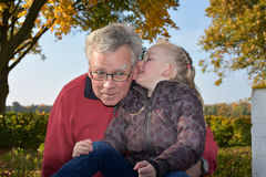 Grandpa is the best. Young and old, grandfather and his granddaughter sharing secrets Stock Images
