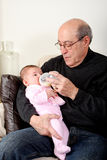 Grandpa bottle feeding baby girl. Caucasian Hispanic Grandfather feeding cute baby girl with a bottle of milk while sitting on a couch in a living room holding Stock Images