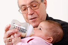 Grandpa bottle feeding baby girl Stock Images