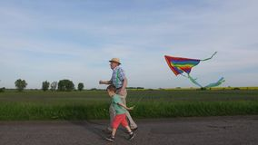 Grandpa with boy running with kite in countryside
