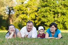 Grandpa, daughters and niece on grass Stock Photo