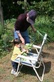 Grandpa de ayuda del muchacho en el jardín imagenes de archivo