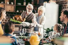 Grandpa with delicious turkey for thanksgiving dinner. With happy family stock images