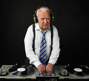 Grandpa dj. A very funky elderly grandpa dj mixing records stock image