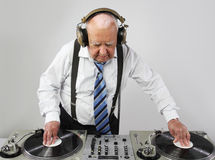 Grandpa dj. A very funky elderly grandpa dj mixing records stock photography