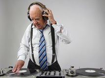 Grandpa dj. A very funky elderly grandpa dj mixing records royalty free stock images