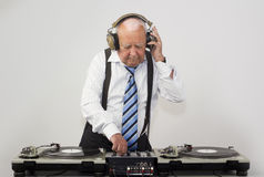 Grandpa dj. A very funky elderly grandpa dj mixing records royalty free stock photo