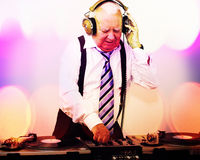 Grandpa dj. A very funky elderly grandpa dj mixing records stock photo