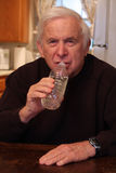 Grandpa drinks from water bottle Royalty Free Stock Photography