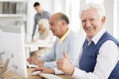 Grandpa enjoys learning. Happy grandpa enjoys learning about modern technology Royalty Free Stock Image
