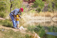 Grandpa fishing with his grandson at a beautiful lake. Grandpa showing his grandson how to fish on a beautiful lake Stock Photo