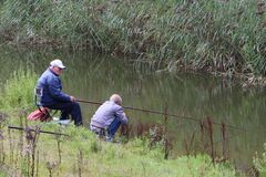 Grandpa fishing with kid Stock Photos