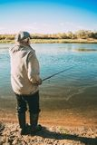 Grandpa is fishing on the river. Grandpa catches fish on the river bank in the open air Stock Photography