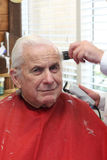 Grandpa gets a haircut. Senior citizen man is getting a trim at the barber shop. He is wearing a red cape and he has white hair. Image is vertical orientation Stock Image