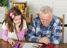 Grandpa and girl study Royalty Free Stock Images