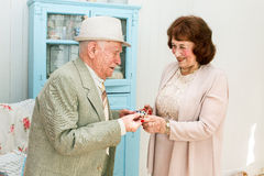 Grandpa gives grandmother jewelry. Royalty Free Stock Images