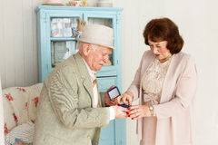 Grandpa gives grandmother jewelry. Stock Image