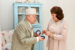 Grandpa gives grandmother jewelry. Stock Images