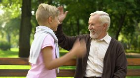 Grandpa gives high-five to grandson, friendship with boy and his upbringing stock video footage