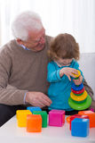 Grandpa and grandchild building tower Stock Photos
