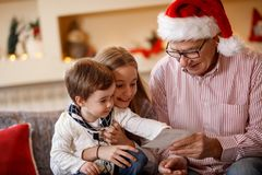 Grandpa with grandchildren looking photo. Grandpa with grandchildren looking Christmas photo Stock Photography