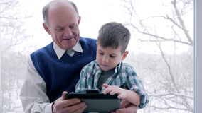 Grandpa and grandchildren play on tablet in computer game indoors