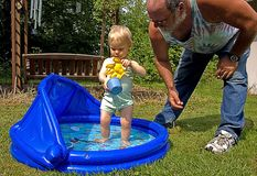 Grandpa and Granddaughter Summertime Fun. This grandpa is helping toddler granddaughter in a kiddie pool for summer time fun Stock Images