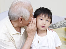 Grandpa and grandson. Asian grandpa telling grandson a secret royalty free stock photos