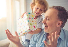 Grandpa and grandson. Cute little boy is giving his grandpa a gift and smiling stock photos