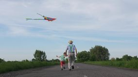 Grandpa with grandson flying kite in countryside