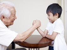 Grandpa and grandson. Grandpa hand wrestling with grandson royalty free stock photos