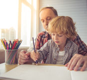 Grandpa and grandson. Handsome grandpa and grandson are smiling while drawing together at home stock photo