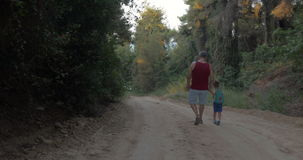 Grandpa and grandson having evening walk in woods. Steadicam back shot of a grandfather and little grandson with backpack holding hands and walking through the stock video footage