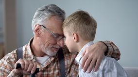 Grandpa and grandson leaning foreheads together, family love, sentimentality stock image