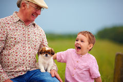 Grandpa and grandson playing with little puppy, summer outdoors Royalty Free Stock Photos