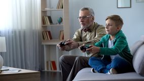 Grandpa and grandson playing video game with console, happy time together royalty free stock photography