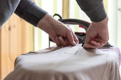 Grandpa help ironing dress for grandma. Focus on aged hands Royalty Free Stock Images