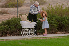 Grandpa helping little girl with hat on walk with toy buggy Stock Images