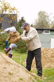 Grandpa helps grandson to get on a sand hill Stock Photo