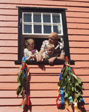 Grandpa with his grandchildren on the window. Grandfather with his grandchildren watch the parade of Jack in the Green festival from their window in Hastings, UK stock images