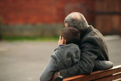 Grandpa and his grandson spend time together in the park. They are sitting on the bench. Back view. Grandpa and his grandson spend time together in the park royalty free stock photo